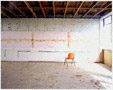 colour photo of chair in derelict building