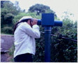 colour photo young woman looking through telescope