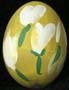 Yellow painted egg with white flowers on green stems